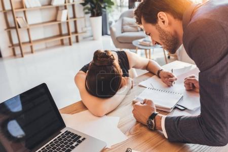 Young secretery crying on desk