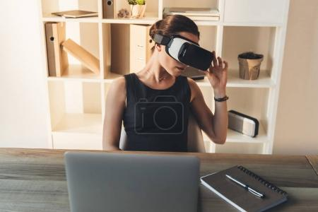 Photo for Young businesswoman in black dress sitting at her desk at office, wearing virtual reality glasses - Royalty Free Image