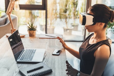 Photo for Young businesswoman in black dress sitting at her desk and using virtual reality glasses - Royalty Free Image