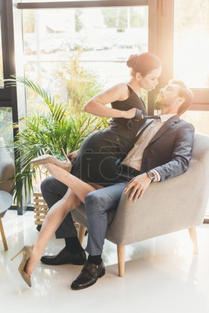 Photo for Young woman in black dress leaning in at the man in suit sitting in armchair - Royalty Free Image
