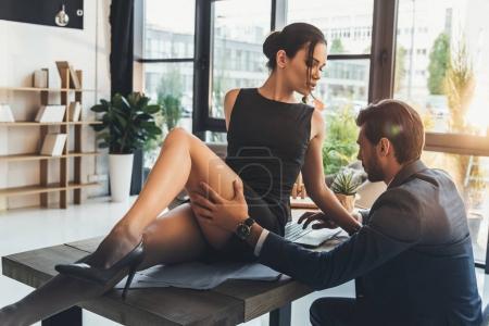 Seductive woman sitting on office desk