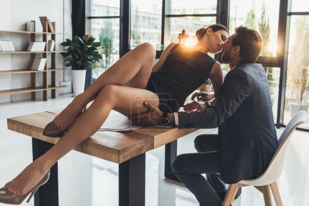 Photo for Young woman in little black dress sitting on a desk in office with man in business suit touching her thigh and leaning in for kiss - Royalty Free Image