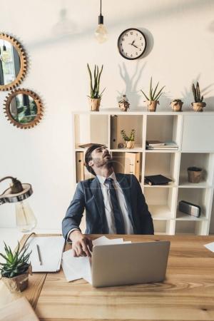 Photo pour Jeune homme assis dans le fauteuil à son bureau la sieste - image libre de droit