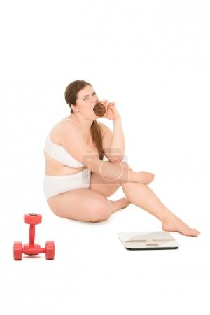 overweight woman with donut, dumbbells and scales
