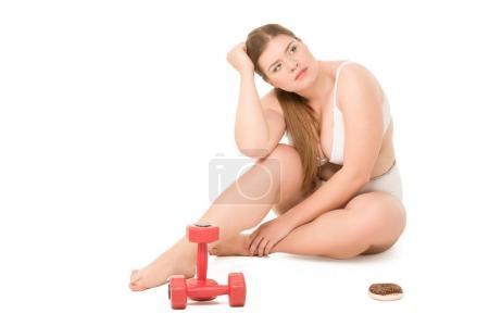 mujer con sobrepeso con rosquilla y mancuernas