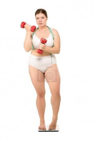 Photo for Overweight woman with measuring tape training with dumbbells and standing on scales, isolated on white - Royalty Free Image