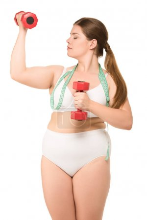 Fat woman with measuring tape and dumbbells