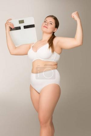 Fat woman posing with scales