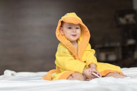Photo for Happy baby boy in yellow robe posing on bed - Royalty Free Image