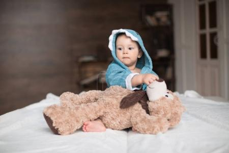 Photo for Happy baby boy in blue robe playing with teddy bear on bed - Royalty Free Image