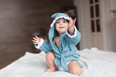 Photo pour Bébé garçon heureux en robe bleue posant sur le lit - image libre de droit