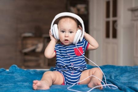 Photo for Funny baby boy wearing white headphones - Royalty Free Image