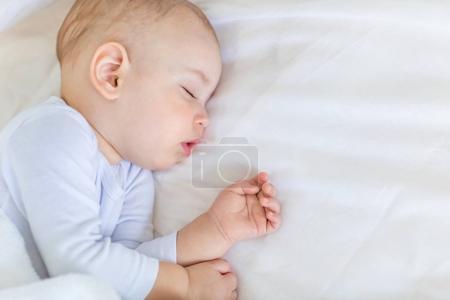 Photo pour Portrait en gros plan d'un adorable bébé garçon dormant au lit, concept de bébé de 1 an - image libre de droit