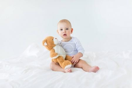Photo for Portrait of adorable small baby boy with teddy bear playing on bed, 1 year old baby concept - Royalty Free Image