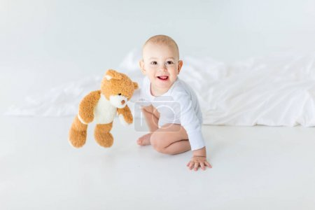 Photo pour Portrait de l'adorable petit bébé garçon avec ours en peluche jouant sur lit, âgé de 1 an, le concept de bébé - image libre de droit