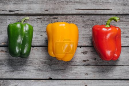 Photo for Top view of colorful bell peppers laying on wooden table, bell peppers - Royalty Free Image