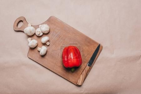 Photo for Top view of bell pepper and mushrooms with knife laying on wooden board, cooking - Royalty Free Image