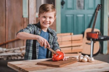 Kid boy cutting bell pepper