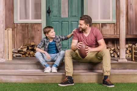 father with son sitting on porch