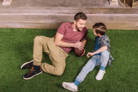 Photo for Father with ball and little son laying on the grass at backyard, dad and son playing - Royalty Free Image