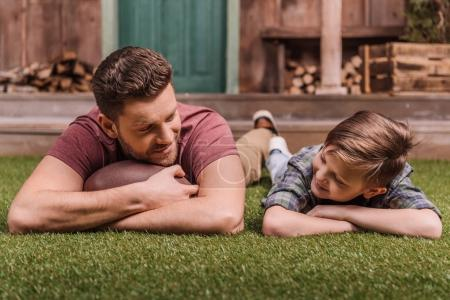 father with son laying on grass