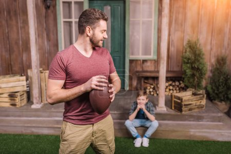 Photo for Father with little son playing american football with ball at backyard, dad and son playing - Royalty Free Image