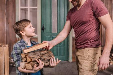 father with son collecting wood logs