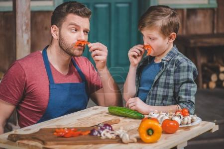 Photo for Father in apron and cute little son having fun with pepper moustaches, dad and son cooking concept - Royalty Free Image