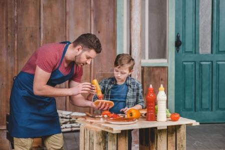 Photo pour Petit garçon mignon avec père dans le tablier préparant hot dog ensemble dans la cour, concept de cuisine papa et fils - image libre de droit