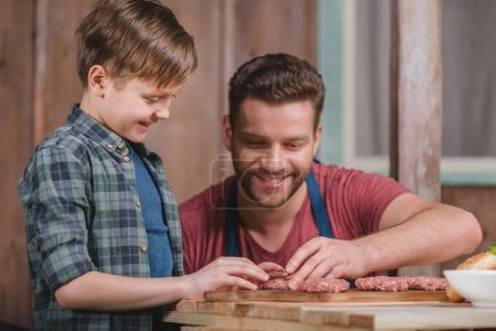 Photo for Happy father and son cooking meat patties together, dad and son cooking concept - Royalty Free Image