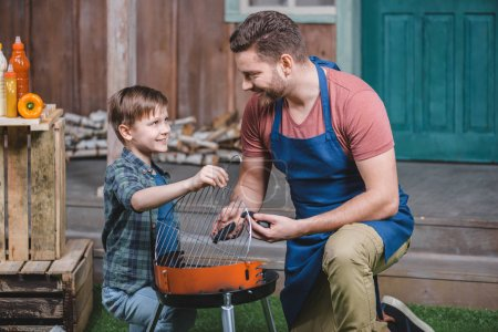 Father and son preparing grill