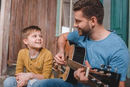 Photo pour Vue latérale de l'homme souriant, jouer de la guitare avec fils près de - image libre de droit