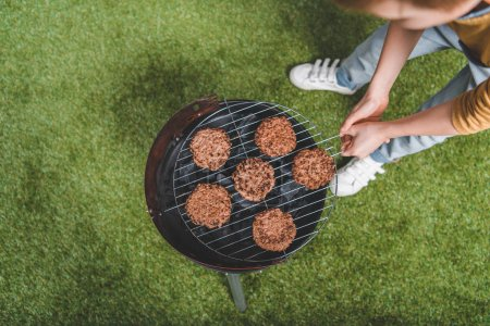 Photo for Partial view of boy cooking meat patties on grill - Royalty Free Image