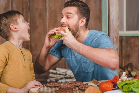 Photo for Side view of man eating homemade burger with little son near by - Royalty Free Image