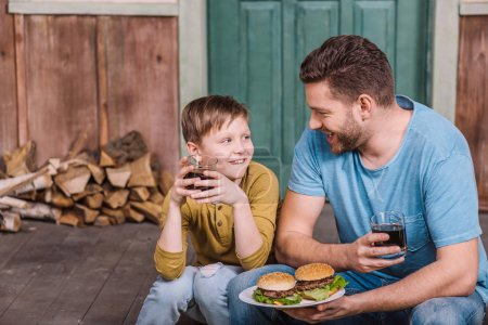 Photo for Portrait of happy father and son eating homemade burgers - Royalty Free Image