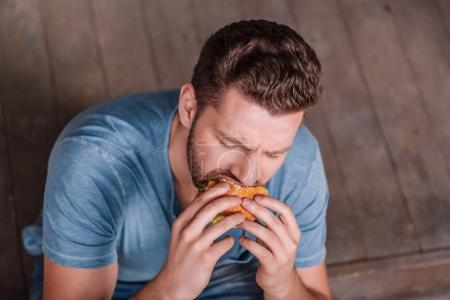 Photo for High angle view of young man eating burger - Royalty Free Image