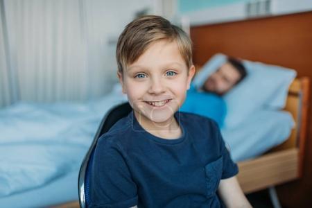 son sitting near sick father at ward