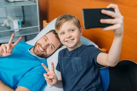 Father and son taking selfie at ward