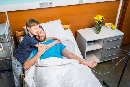 Photo pour Père avec fils embrassant tout allongé sur le lit d'hôpital à la salle, papa et fils - image libre de droit
