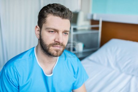 sick man sitting on hospital bed