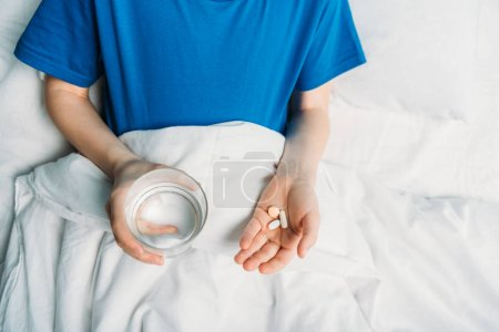 Boy with glass of water and medicines