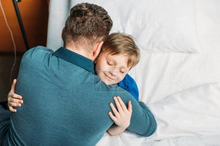 little son hugging father