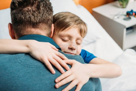 Photo for Portrait of little son hugging father in hospital chamber - Royalty Free Image