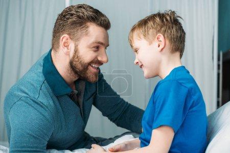 Foto de Vista lateral de padre e hijo mirando el uno al otro en la sala de hospital - Imagen libre de derechos