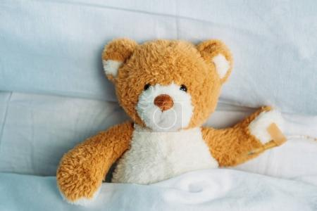 Photo for Close up view of cute teddy bear toy lying in bed with drop counter - Royalty Free Image