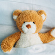 Close up view of cute teddy bear toy lying in bed ...