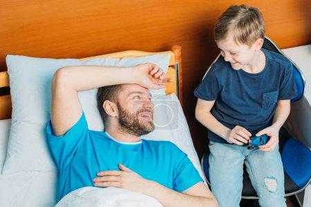 Foto de Sonrisa de padre e hijo mirando el uno al otro en la sala de hospital - Imagen libre de derechos