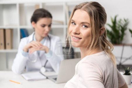 Photo for Close-up view of beautiful young patient smiling at camera and doctor using laptop behind - Royalty Free Image
