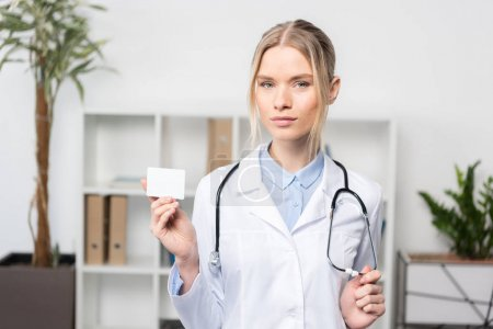 Foto de Confiado joven médico sosteniendo la tarjeta de visita en blanco y mirando a la cámara - Imagen libre de derechos