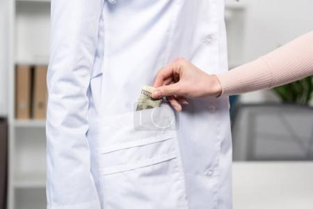 patient putting money into doctor's pocket